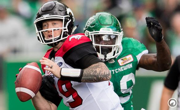 Bo Levi Mitchell of the Calgary Stampeders is about to be sacked by A.C. Leonard of the Saskatchewan Roughriders