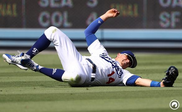 Outfielder Enrique 'Kike' Hernandez #14 of the Los Angeles Dodgers makes the sliding catch on a flyball hit to right field by David Fletcher #6 of the Los Angeles Angels of Anaheim (not in photo) during the ninth inning of the MLB game at Dodger Stadium on July 15, 2018 in Los Angeles, California.