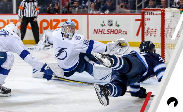 Nikolaj Ehlers #27 of the Winnipeg Jets falls to the ice as he shoots the puck into the net past goaltender Andrei Vasilevskiy #88 of the Tampa Bay Lightning for a third period goal at the Bell MTS Place on December 16, 2018 in Winnipeg, Manitoba, Canada.