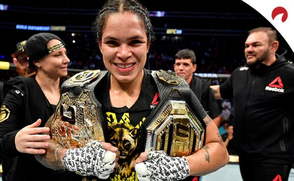 Amanda Nunes celebrates with her two belts after beating Germain De Randamie