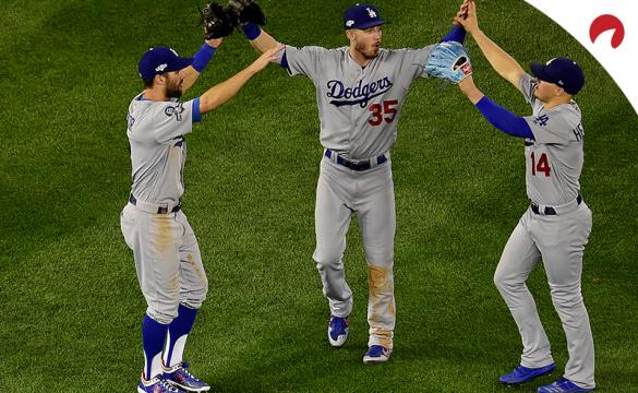 Three Los Angeles Dodgers players celebrating in the outfield after a win