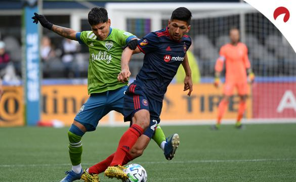 MLS Is Back Tournament Odds Two soccer players jostling for the ball at midfield