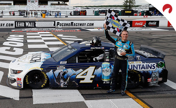 Kevin Harvick celebrating with the checkered flag in front of his car at Pocono Raceway
