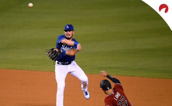 Gavin Lux #9 of the Los Angeles Dodgers makes a throw over Jake Lamb #22 of the Arizona Diamondbacks.