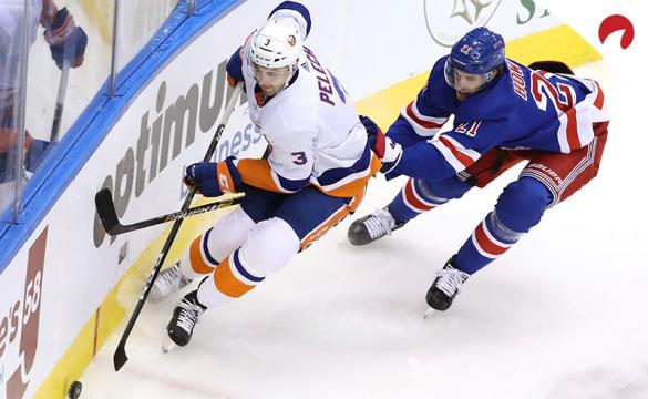 Adam Pelech #3 of the New York Islanders wraps around the net as Brett Howden #21 of the New York Rangers.