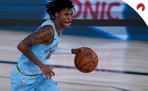 Ja Morant running up the basketball court with a basketball in hand.