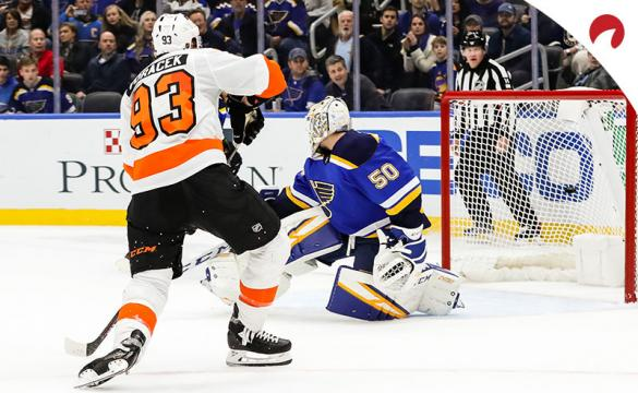 Philadelphia Flyers' Jakub Voracek, left, gets the puck past St. Louis Blues goaltender Jordan Binnington (50) for a goal and the win during the overtime period of an NHL hockey game between the St. Louis Blues and the Philadelphia Flyers.