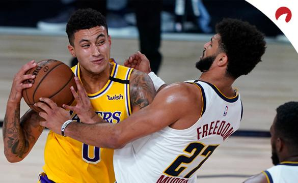 Kyle Kuzma (0) of the Los Angeles Lakers drives to the basket against Jamal Murray (27) of the Denver Nuggets during an NBA game on August 10, 2020, in Lake Buena Vista, Florida.