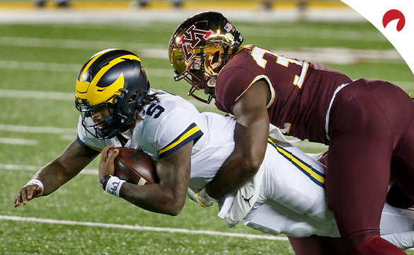 Michigan quarterback Joe Milton (5) leaps forward as Minnesota defensive lineman Boye Mafe (34) tackles him during an NCAA college football game Saturday, Oct. 24, 2020, in Minneapolis.