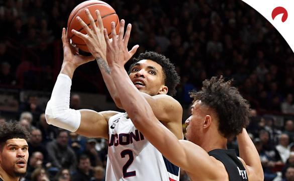 Connecticut's James Bouknight (2) shoots over Cincinnati's Zach Harvey, right, as Cincinnati's Jarron Cumberland, left, looks on in an NCAA college basketball game on Sunday, Feb. 9, 2020, in Storrs, Conn.