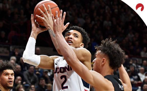 Connecticut's James Bouknight (2) shoots over Cincinnati's Zach Harvey, right, as Cincinnati's Jarron Cumberland, left, looks on in an NCAA college basketball game on Sunday, Feb. 9, 2020, in Storrs, Conn.