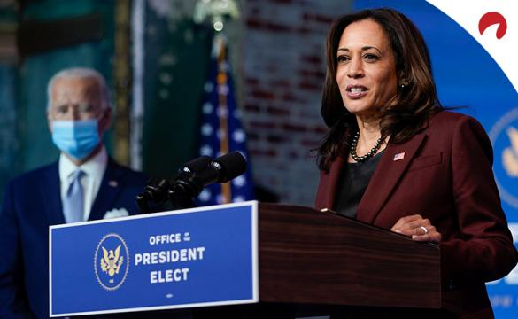Kamala Harris, who leads the 2024 U.S. presidential election odds, gives a speech at a Democratic Party rally with Joe Biden looking on.