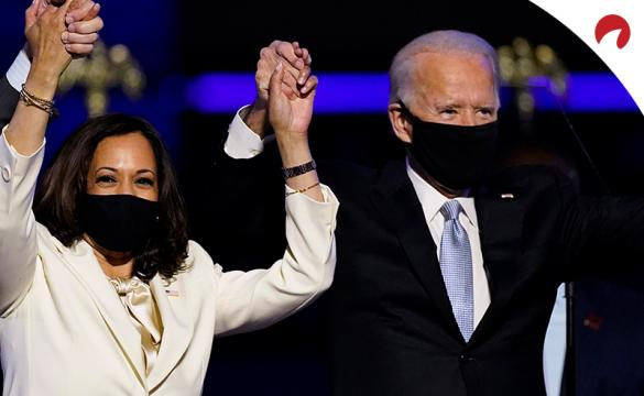 Joe Biden and Kamala Harris raising hands in triumph from their 2020 presidential win