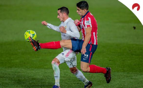 Luis Suárez y Lucas Vázquez disputan un balón. Conoce las cuotas y pronósticos para el Atlético de Madrid Vs Real Madrid
