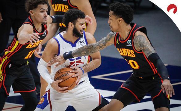 Jamal Murray esconde el balón ante dos rivales. Descubre las cuotas para el Nuggets Vs 76ers de la NBA.
