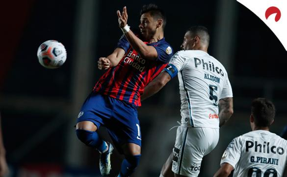 Angel Romero y Alison disputan un balón aéreo. Conoce las cuotas del Santos Vs San Lorenzo.