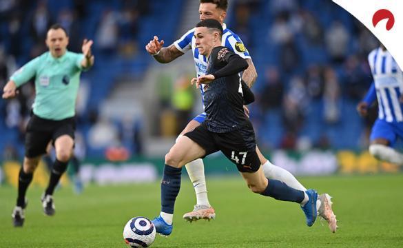 Phil Foden controla un balón perseguido por un rival. Conoce las cuotas y pronósticos del Manchester City Vs Everton.
