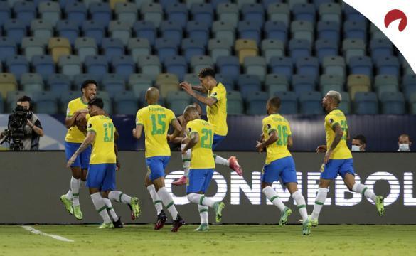 Eder Militao celebra un gol junto a sus compañeros de la Canarinha. Cuotas y picks Brasil vs Chile.
