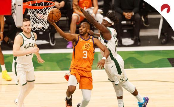 Chris Paul (izquierda) anota ante Jrue Holiday en las finales de la NBA. Conoce los pronósticos del Suns vs Bucks.