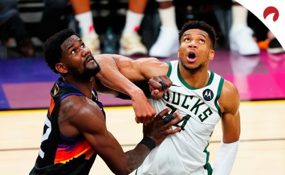 Deandre Ayton (izquierda) y Giannis Antetokounmpo tratan de coger un rebote. Mira los pronósticos del Bucks vs Suns.
